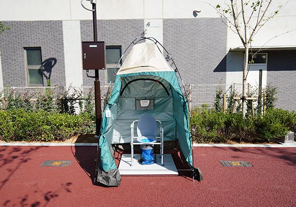 小さなテントの中にマンホールトイレが設置されています。災害時に利用できます。